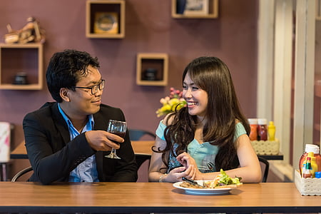 man and woman eating dinner on brown wooden table