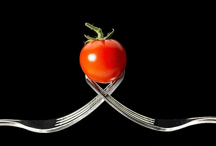 photo of tomato between the tips of two forks