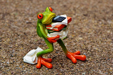 green frog carrying paper documents figurine on ground