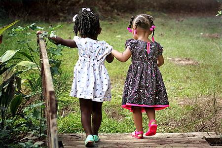 two girls walking on bridge