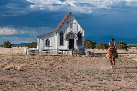 man riding horse near church