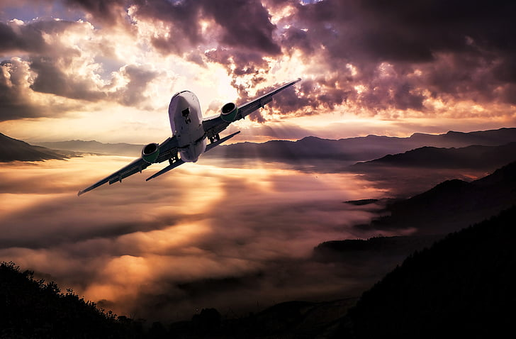 airliner in mid air above mountains