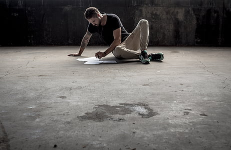 man and blue and brown clothes sitting on gray concrete pavement