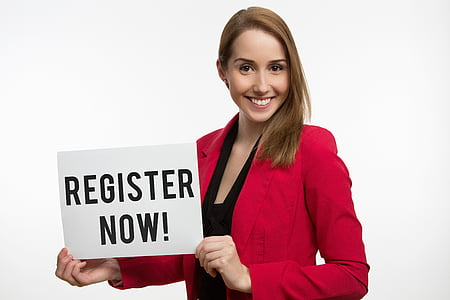 woman wearing red blazer holding register now signage