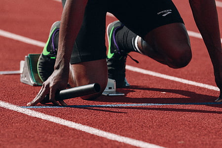 person wearing black-and-green Nike running shoes kneeling on starting line