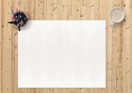 white blank paper below pen organizer beside cup of coffee