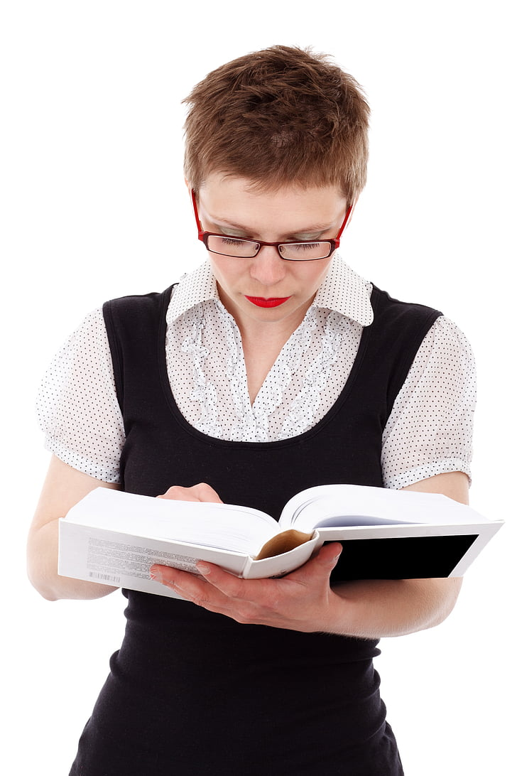 woman holding white hardbound book