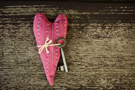 silver key attached on heart pillow