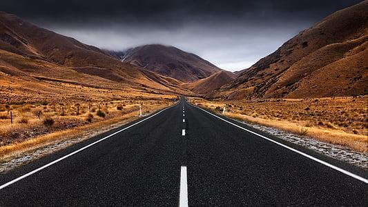 gray empty road under nimbus clouds