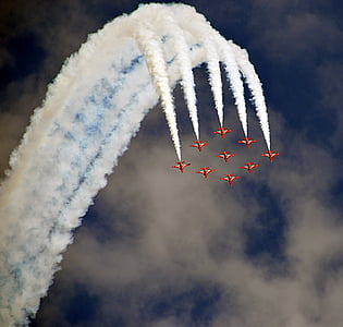 nine red jet plane with doing air shore during daytime
