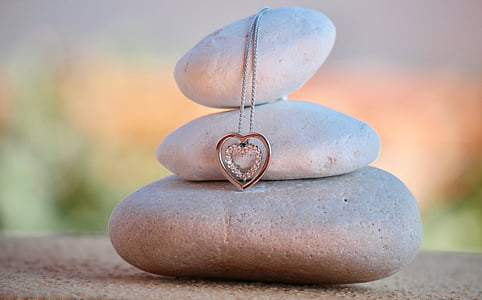 shallow focus photography of silver-colored heart pendant