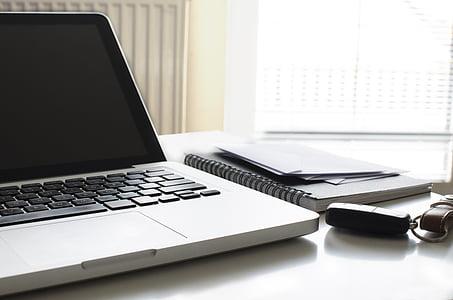 powered-off MacBook Pro beside notebook