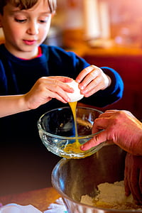 boy breaking an egg over a bowl