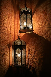 two turned on candle lanterns