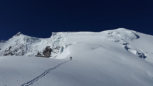 person walking on snow capped mountain