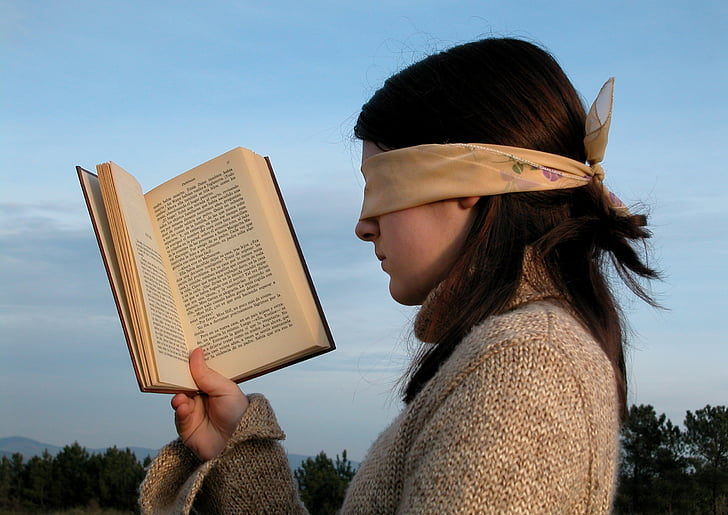 woman wearing white blindfold holding book during daytime