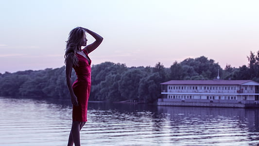 woman wearing red mini dress standing beside body of water during golden hour