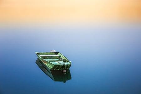 green jon boat on body of water