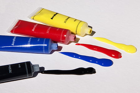 four yellow, red, blue, and black color labeled soft tube bottles