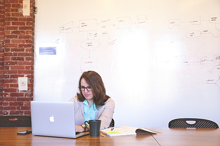 photo of woman wearing grey blazer sitting on chair in front of MacBook