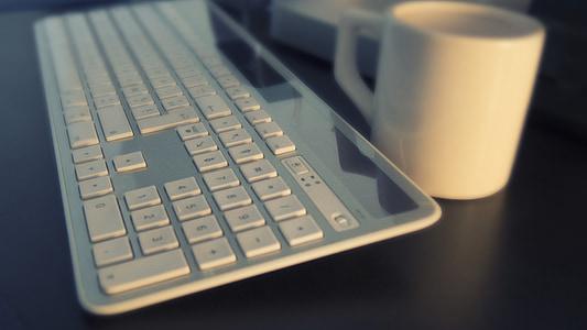 white wireless computer keyboard and white mug