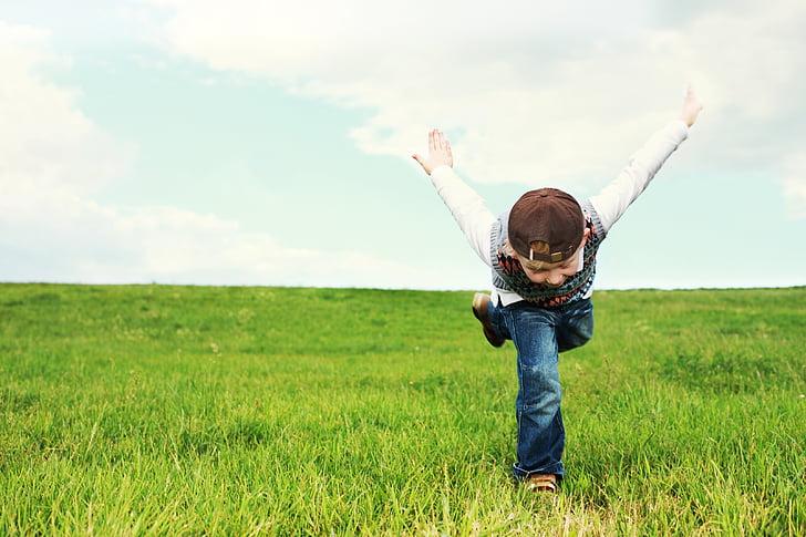 boy running like ninja on grass during daytime
