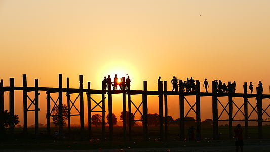 silhouette of people on wooden dock during sunset