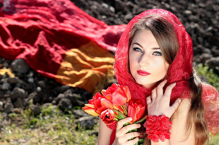 woman holding bouquet of red flowers wearing red headdress