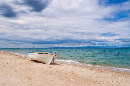 white rowboat in seashore