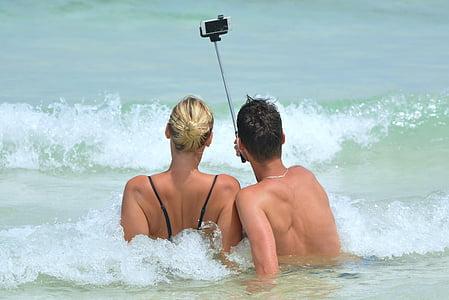 man and woman on beach taking selfie using monopod stick