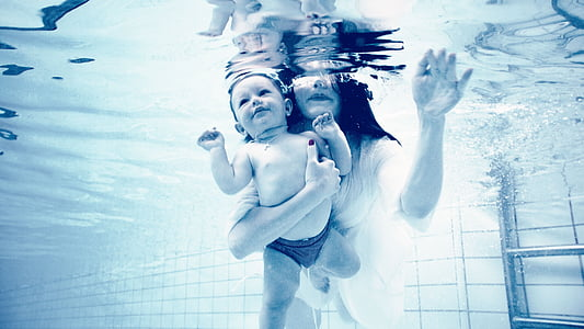 woman holding baby while underwater