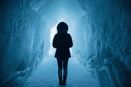 person in winter jacket standing inside the ice cave