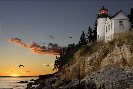 low angle view of lighthouse near body of water during golden hour