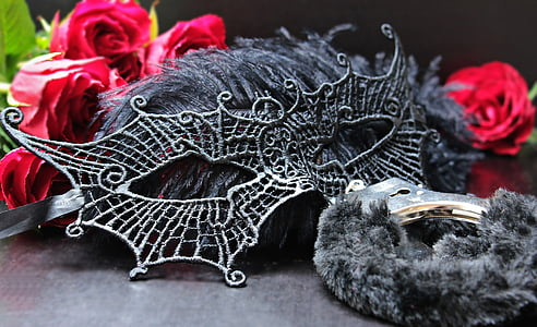 black masquerade mask surrounded by red Rose flowers