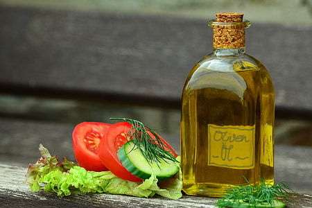 olive oil bottle and sliced tomatoes in shallow focus photography