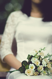 bouquet of white flowers on lap of a woman