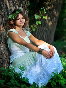 woman in white and green cap-sleeved dress lying on tree