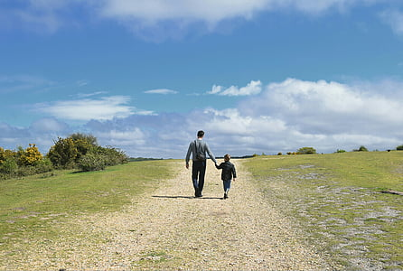 man holding children while walking on green grass field
