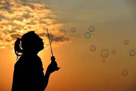 woman silhouette making bubbles