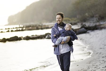 man carrying baby near seashore during daytime