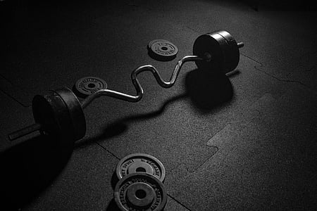 grayscale photo of ez curl barbell and weight plates