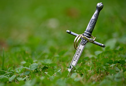 silver-colored sword on green grass