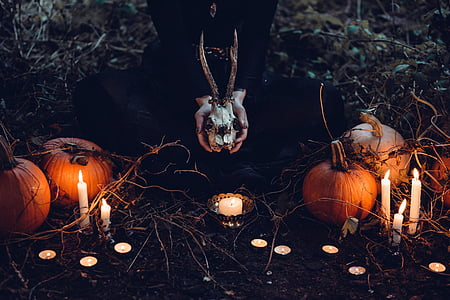 female laying on floor beside pumpkins with lighted candles