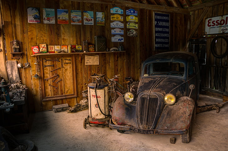rusty brown Volkswagen Beetle near air compressor and brown wooden wall
