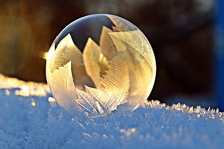 shallow focus of clear glass ornament on snow