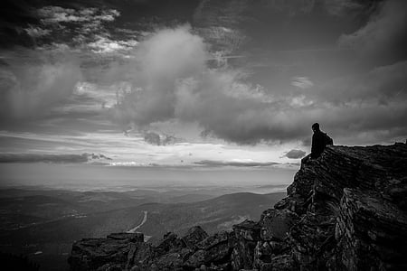 man sitting on rocky cliff looking at mountains in grayscale photography