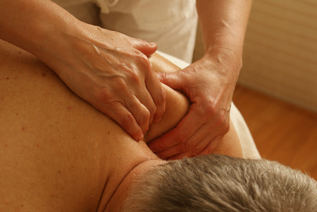 person standing beside lying man massaging his back