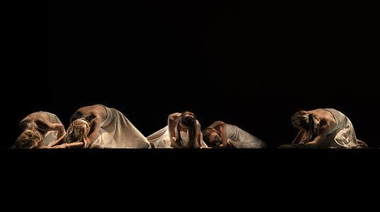 five women wearing white dress kneeling on floor