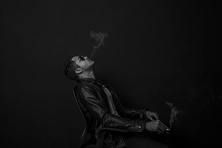 man wearing black leather jacket while blowing smoke on cigarette