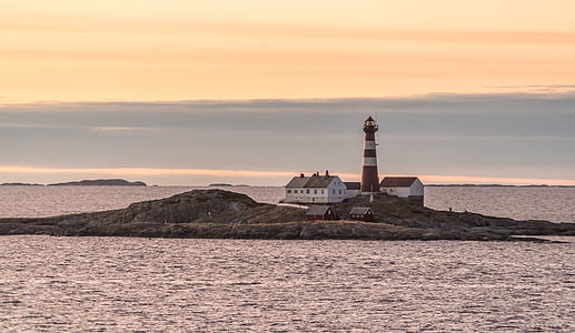 white and red lighthouse on island during sunset